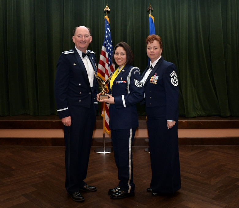 Col. Thomas K. Smith, 433rd Airlift Wing commander, and 433rd AW Command Chief Master Sgt. Shana C. Cullum, award Tech. Sgt. Stephanie Escobedo, 433rd Aerospace Medicine Squadron, as the Honor Guard Member of the Year at the 433rd AW annual awards banquet at Joint Base San Antonio-Lackland, Texas Feb. 9, 2019.