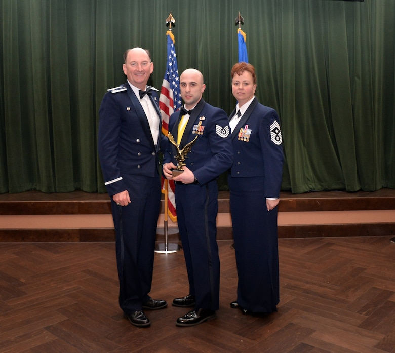 Col. Thomas K. Smith, 433rd Airlift Wing commander, and 433rd AW Command Chief Master Sgt. Shana C. Cullum, award Tech. Sgt. Anthony Martin, 433rd Force Support Squadron, as the Noncommissioned Officer of the Year at the 433rd AW annual awards banquet at Joint Base San Antonio-Lackland, Texas Feb. 9, 2019.