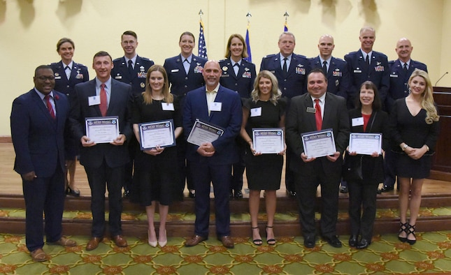 Leadership from the 403rd Wing pose for a group photo with the newly inducted honorary commanders during the 2019 Honorary Commander Induction Ceremony inside the Bay Breeze Event Center at Keesler Air Force Base, Mississippi, Feb. 9, 2019. The event recognized the newest members of Keesler's honorary commander program, which is a partnership between military commanders and local civic and business leaders in order to enrich and strengthen the relationship between the base and the community. This was the first time leadership from the 2nd Air Force, 81st Training Wing and 403rd Wing combined to host a single joint induction ceremony. (U.S. Air Force photo by Kemberly Groue)