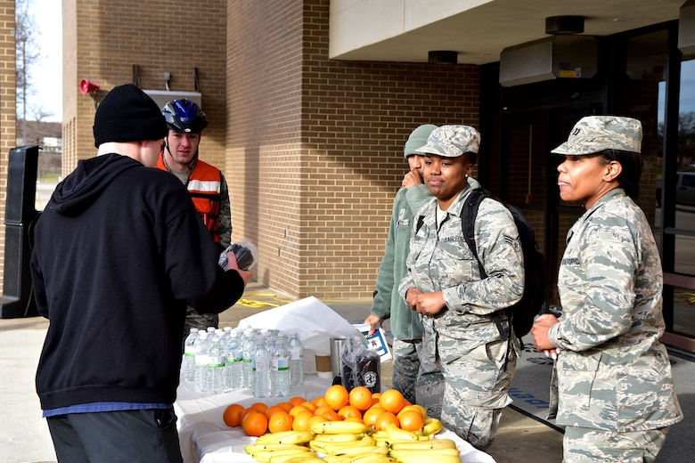 Airmen set up stand with oranges and bananas.