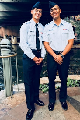 2 Airmen pose for photo after basic military training graduation.