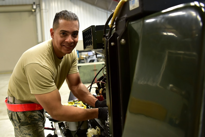 Airman poses for a photo next to a machine.