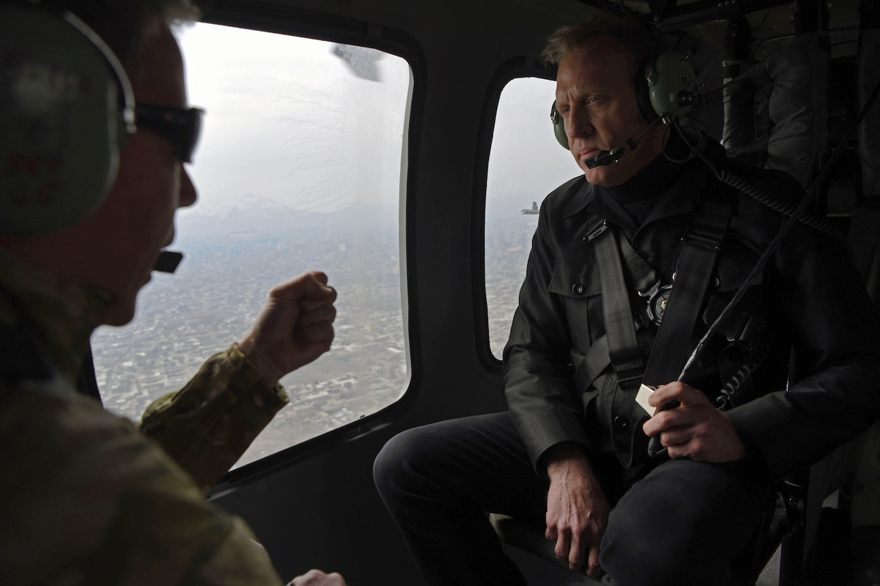 Two men talk on board a helicopter.