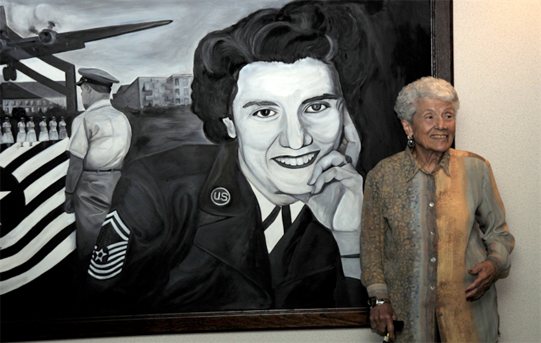 Retired Chief Master Sgt. Grace Peterson stands in front of a painting of herself in front of the Grace Peterson Hall at the U.S. Air Force Expeditionary Center Oct. 18, 2010, at Joint Base McGuire-Dix-Lakehurst, N.J.