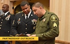 Sheriff and Army soldier read a community partnership booklet together.