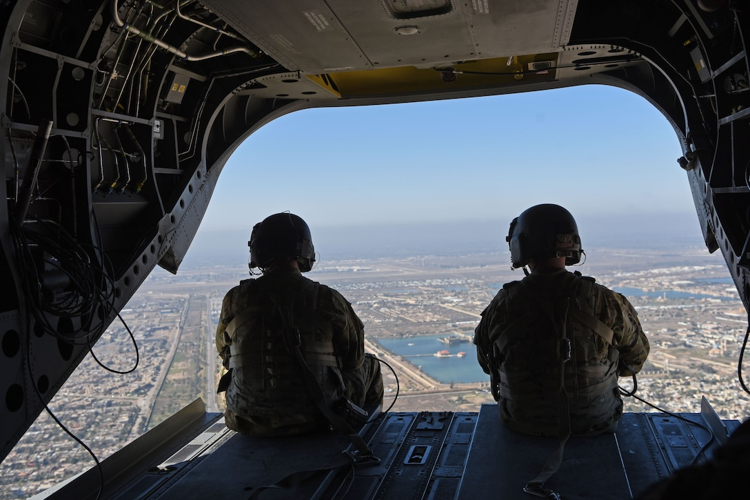 Two U.S. troops sit in a helicopter looking out over a city.