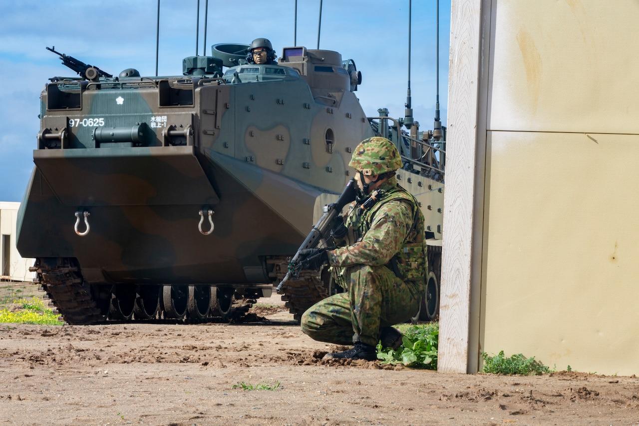 A Japan Ground Self-Defense Force soldier patrols alongside an assault amphibious vehicle.