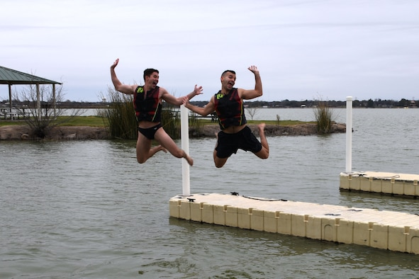 U.S. Air Force 2nd Lt. Christian Gilbert and 2nd Lt. Christian Nazario, 315th Training Squadron students, strike a pose before hitting the 42 degree water of Lake Nasworthy at the annual Polar Bear Run and Swim at the Goodfellow Recreation Camp Feb. 9, 2019. After plunging into the lake participants could enjoy S'mores and food by a fire. (U.S. Air Force photo by Senior Airman Seraiah Hines/Released)