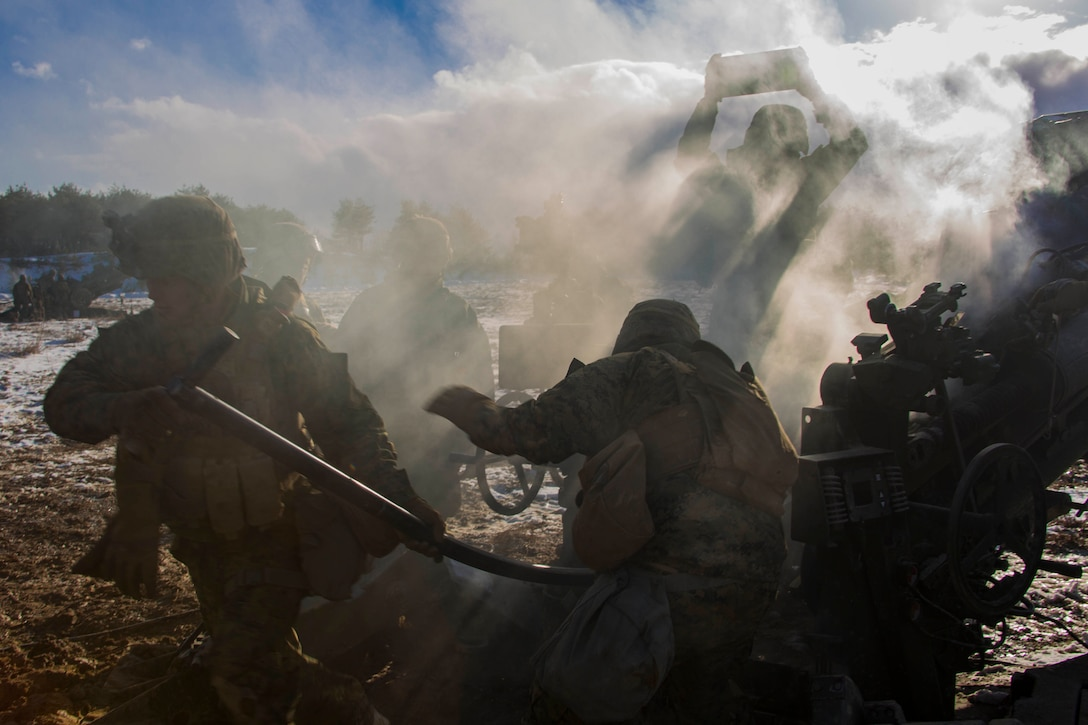 Marines load shells into a howitzer.