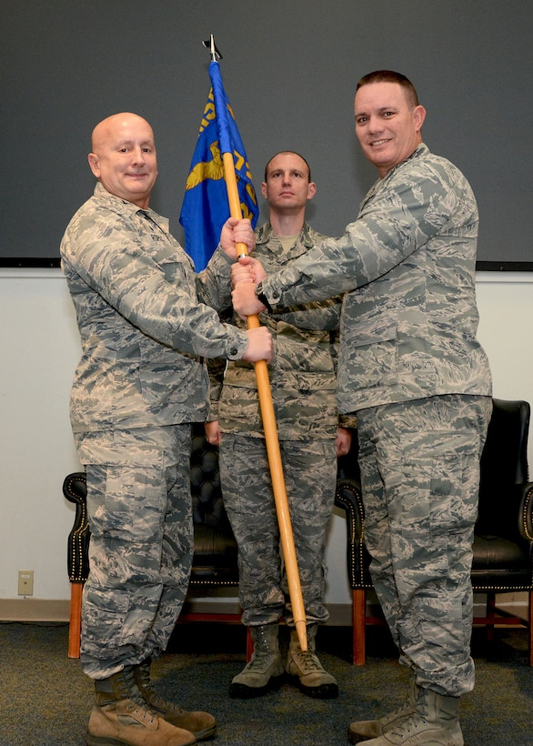 Lt. Col. William Young, right, relinquishes command of the 72nd Aerial Port Squadron Feb. 10, 2019, at Tinker Air Force Base, Oklahoma to Col. Richard Ropac, 507th Mission Support Group commander, who passed the guidon to Col. Darryl McLean moments later. (U.S. Air Force photo by Tech. Sgt. Samantha Mathison)
