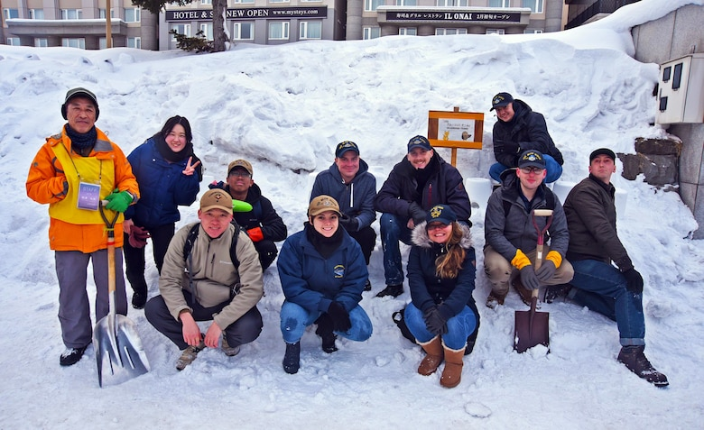 Blue Ridge and 7th Fleet snow lantern event volunteers pose for a group photo with the event coordinators in Otaru, Japan.