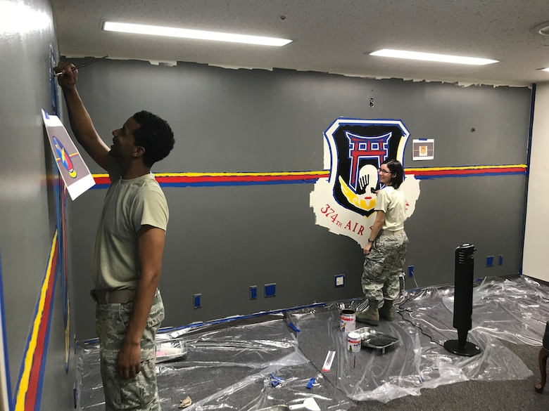 Tech Sgt. Adam Bethea, 374th Operations Support Squadron aircrew flight equipment craftsman, and then Senior Airman Darion Duverney, 374 OSS weather journeyman, paint a mural in the conference room at Yokota Air Base, Japan, Jul. 20, 2018.
