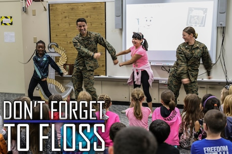 "Navy Lt. Kristopher Zamora, center left, and Lt. Kathryn Harrington, right, do the ""floss"" dance with students from Kinser Elementary School Feb. 5, 2019 on Camp Kinser, Okinawa, Japan. Sailors from Naval clinics in Okinawa held a presentation to promote oral health awareness during National Children's Dental Health Month. Zamora, a general dentist with Branch Dental Clinic Hansen, 3rd Dental Bn., 3rd Marine Logistics Group, is a native of Caldwell, Idaho. Harrington, a general dentist with Branch Dental Clinic Futenma, 3rd Dental Bn., 3rd MLG, is a native of Cleveland, Ohio. (U.S. Marine Corps photo by Armando Elizalde)"