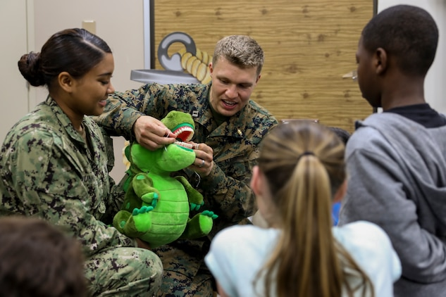 Navy Lt. Michael J. Lawrence, center left, and Seaman Lauryn A. Dunning, left, demonstrate how to properly floss teeth to students from Kinser Elementary School Feb. 5, 2019 on Camp Kinser, Okinawa, Japan. Sailors from Naval clinics in Okinawa held a presentation to promote oral health awareness during National Children's Dental Health Month. Lawrence, a general dentist with Branch Dental Clinic Evans, 3rd Dental Battalion, 3rd Marine Logistics Group, is a native of Troutdale, Oregon. Dunning, a hospital corpsman with Branch Dental Clinic Futenma, 3rd Dental Bn., 3rd MLG, is native of New Orleans, Louisiana. (U.S. Marine Corps photo by Lance Cpl. Armando Elizalde)