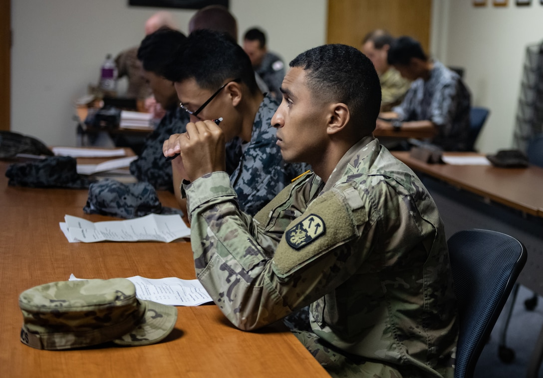 Japan Air Self-Defense Force Airmen and U.S. service members listen to a briefing Nov. 19, 2018, during the 2018 Bilateral Exchange at Kadena Air Base, Japan. The event included professional enhancement seminars, physical training, a tour of an MC-130H Combat Talon II, an infiltration and exfiltration demonstration, a historical tour and team building exercises. (U.S. Air Force photo by Staff Sgt. Micaiah Anthony)