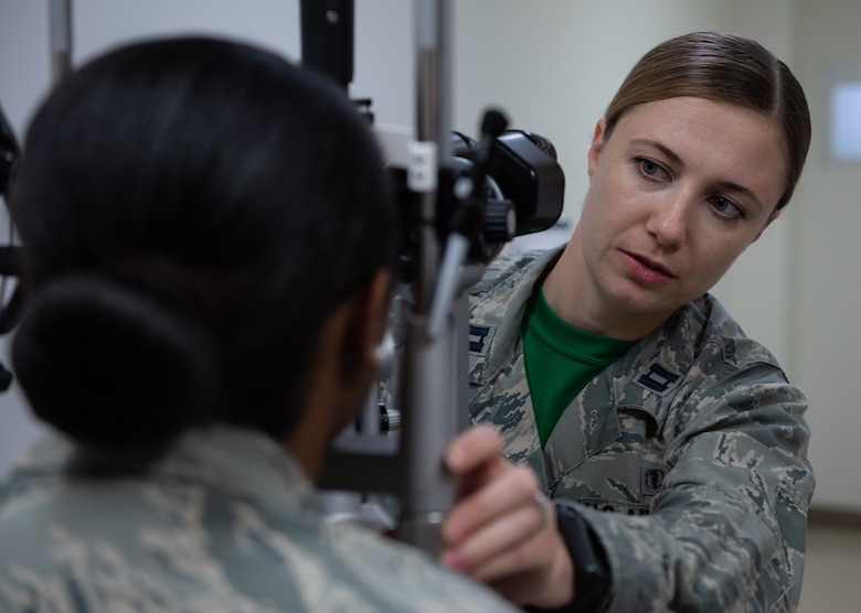 U.S. Air Force Capt. Suzanne Romeo, 18th Aerospace Medicine Squadron operational optometry chief, prepares to conduct an eye exam on Airman 1st Class Praise Butler-Davis, 18th AMDS optometry technician, Jan. 11, 2019, at Kadena Air Base, Japan. Optometrists provide primary eye care by testing people's eyes for visual acuity and eye diseases. (U.S. Air Force photo by Staff Sgt. Micaiah Anthony)