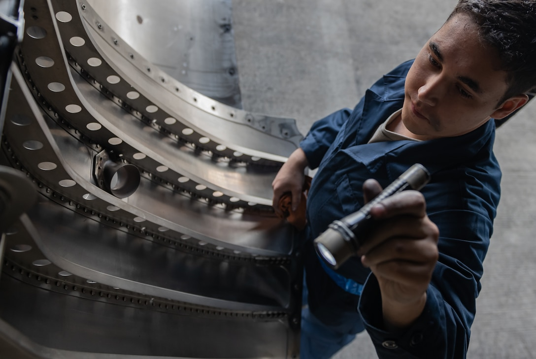U.S. Air Force Airman 1st Class Jack O'Connell, 18th Aircraft Maintenance Squadron crew chief, inspects an F-15 Eagle engine bay compartment, Jan. 18, 2019, on Kadena Air Base, Japan. Airmen from the 18th AMXS cleaned the engine bay to help them identify and repair cracks and gouges. (U.S. Air Force photo by Staff Sgt. Micaiah Anthony)