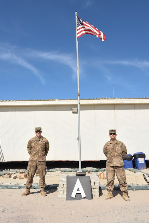 Private 1st Class Matthew Burke, Bravo Battery, 1st Battalion, 43rd Air Defense Artillery Regiment in charge of Bravo Command Post records, and Specialist Casey Bearden, B/1-43 ADA enhanced early warning systems operator, pose for a photo at Al Dhafra Air Base, United Arab Emirates, Jan. 12, 2019.