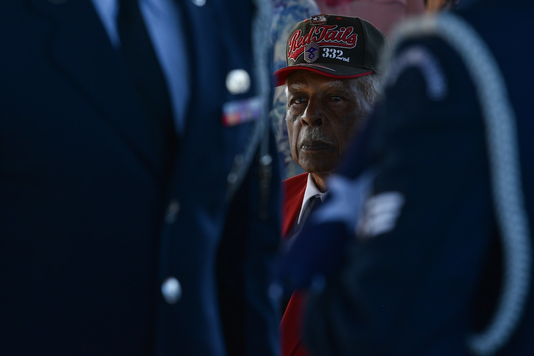 A Tuskegee Airmen chapter member watches Patrick Air Force Base Honor Guard Airmen present the colors during a Tuskegee Airman funeral, Feb. 7, 2019 at Cape Canaveral National Cemetery in Mims, Fla. Edwin Cowan, Tuskegee Airman, was laid to rest with his wife with military honors. (U.S. Air Force photo by Airman 1st Class Dalton Williams)