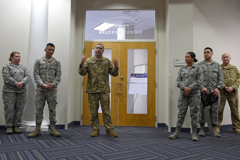 A bunch of Airman stand in front a two doors inside a building