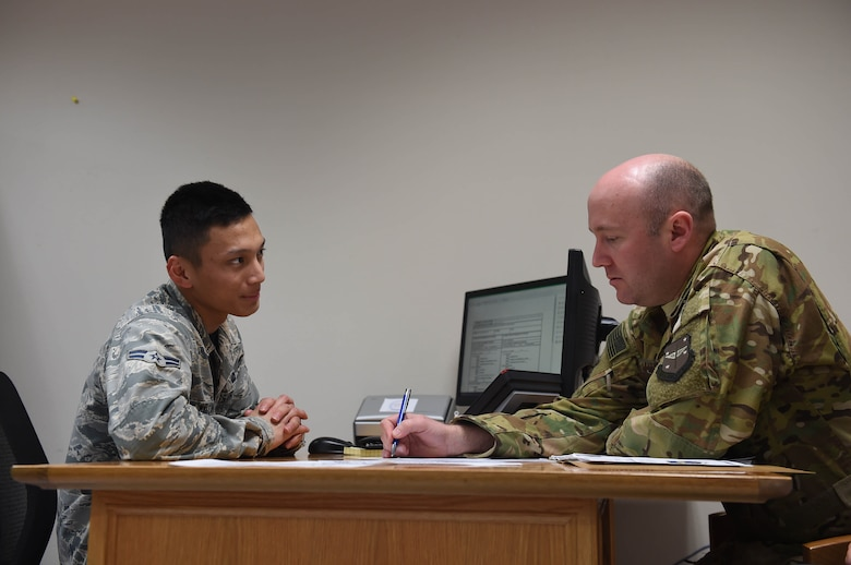 Two Airmen sit a desk with a computer