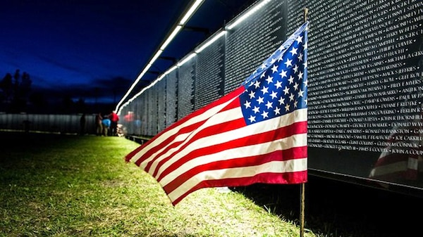 """Like the original memorial, """"The Wall That Heals"""" is erected in a chevron shape and visitors can do name rubbings of individual service member's names. The replica is constructed of Avonite, a synthetic granite, and its 140 numbered panels are supported by an aluminum frame. Machine engraving of the more than 58,000 names along with modern LED lighting provide readability day and night."""