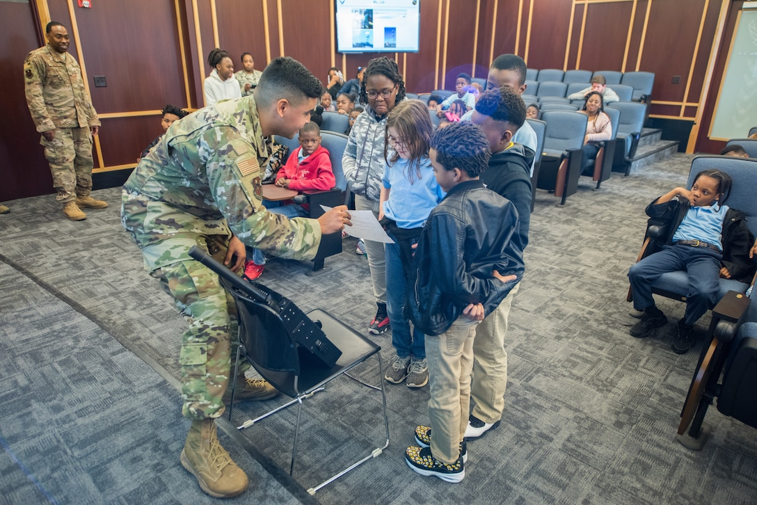 Senior Airman Emanuel Leon–Santiago, 42nd Operational Support Squadron air traffic controller, demonstrates how air traffic controllers speak to pilots flying in their airspace to a group of students from Thelma S. Morris Elementary School Feb. 5, 2019, Maxwell Air Force Base, Alabama. Students in grades three through five had an opportunity to visit the 42nd OSS and meet the Airmen who make the mission happen. (U.S. Air Force photo by Senior Airman Alexa Culbert)