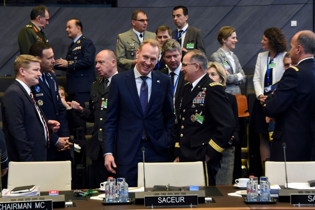 Acting Defense Secretary Patrick M. Shanahan talks to Army Gen. Curtis M. Scaparrotti with people in the background.