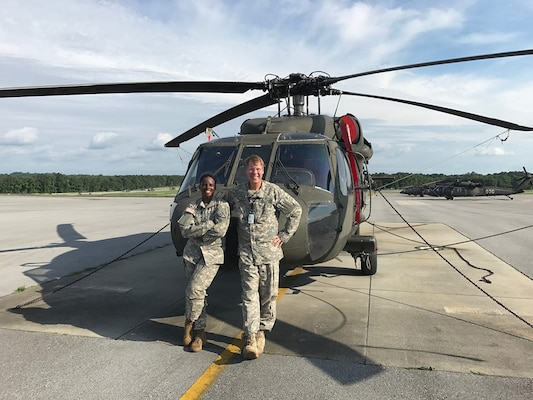 Warrant Officer Cicely Williams, left, takes time out for a photo with Randy Welch, an instructor pilot, in front of a UH-60 Black Hawk.