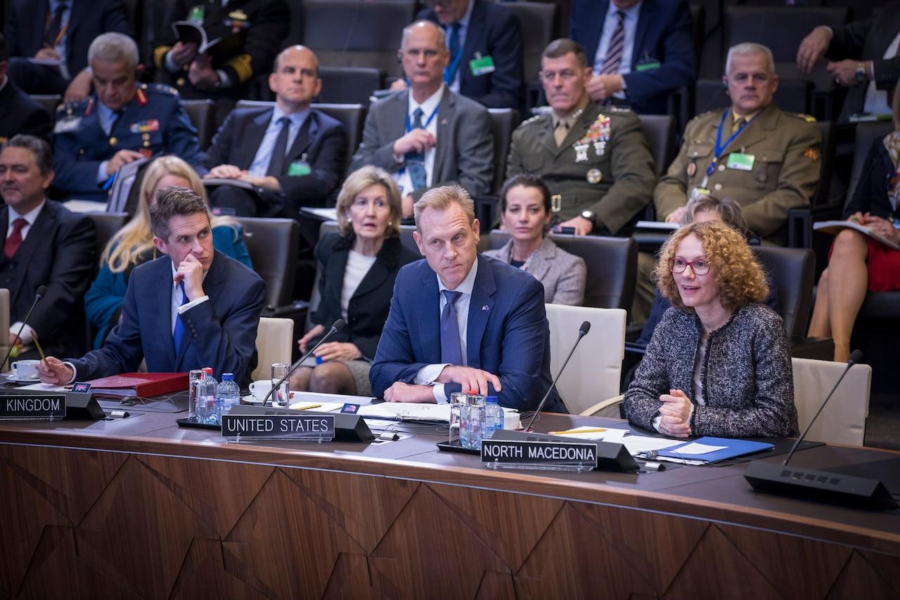 Acting Defense Secretary Patrick M. Shanahan sits in between two people.