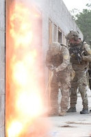 Staff Sgt. Ethan Johnson, an explosives ordnance technician in the 119th Wing, detonates an explosive tool which had been placed on a door as Senior Airman Tyler Herlihy, a tactical air control party (TACP) Airman in the 169th Air Support Operations Squadron (ASOS), provides support as they prepare to breach a door while conducting training during Exercise Southern Strike 19 at Camp Shelby Joint Forces Training Center near Hattiesburg, Miss., Jan. 18, 2019.