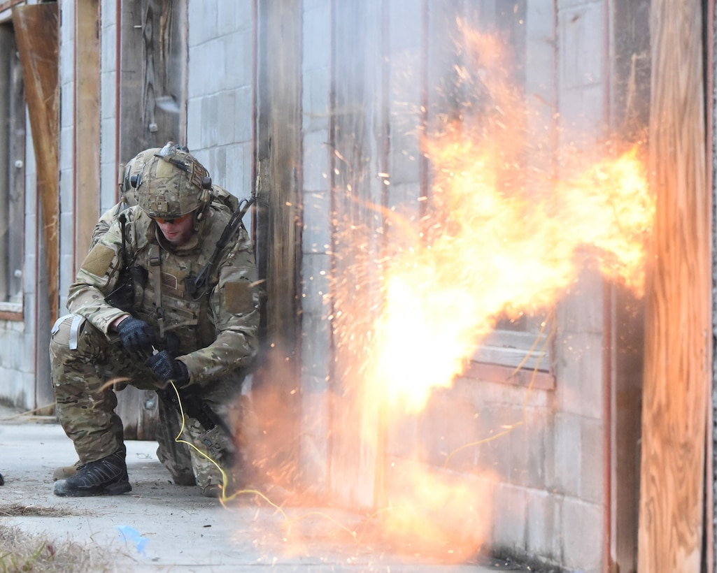 Senior Airman Tyler Herlihy, a tactical air control party (TACP) Airman in the 169th Air Support Operations Squadron (ASOS), detonates an explosive tool mounted on a door as Staff Sgt. Ethan Johnson, an explosives ordnance technician in the 119th Wing, provides support as they prepare to breach a door while conducting training during Exercise Southern Strike 19 at Camp Shelby Joint Forces Training Center near Hattiesburg, Miss., Jan. 18, 2019.