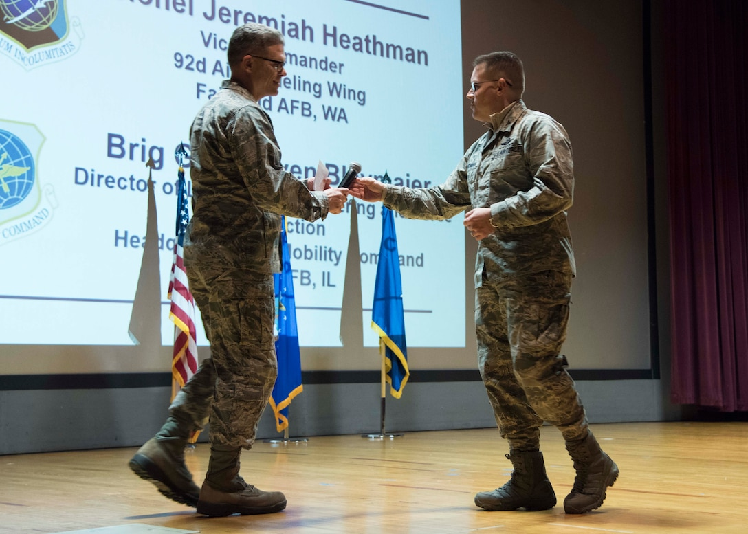 U.S. Air Force Brig. Gen. Steven Bleymaier, Air Mobility Command Logistics, Engineering and Force Protection director, is handed a microphone by Col. J. Scot Heathman, 92nd Air Refueling Wing vice commander, before addressing attendees at the Mobility Guardian 2019 International Planning Conference held at Fairchild Air Force Base, Washington, Feb. 5, 2019.