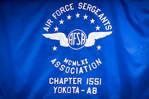 The Air Force Sergeants Association Chapter 1551 Yokota Air Base flag hangs on a wall during the second annual Mentoring Up event, Feb. 7, 2018, at Yokota Air Base, Japan. Mentoring up is sponsored by the AFSA and provides a unique opportunity for ambitious Airmen who are leading their tier to present pressing matters and innovative ideas to senior enlisted leaders. (U.S. Air Force photo by Senior Airman Donald Hudson)