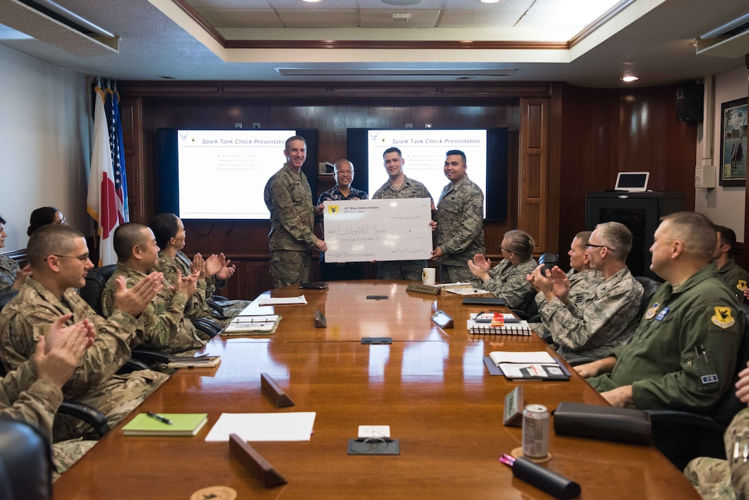 U.S. Air Force Brig. Gen. Case A. Cunningham, 18th Wing commander, presents a check for $2,500 to the 2018 Shogun Spark Tank winners for their contingency lodging application, LodgeNET, on Feb. 11, 2019 at Kadena Air Base, Japan. Innovative incentive programs such as the 18th WG Spark Tank encourage Airmen to think outside the box and provide new solutions to everyday problems.