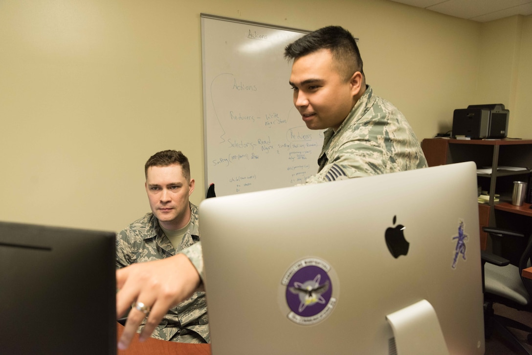 U.S. Air Force Tech. Sgt. Christopher Sills, 18th Communication Squadron programmer, and Staff Sgt. Alexander Nestle, 18th CS software development supervisor, work on LodgeNET, a contingency lodging application on Feb. 12, 2019 at Kadena Air Base, Japan. LodgeNET provides real-time contingency statistics in one collaborative platform, and consolidates data 99% faster than manual input.