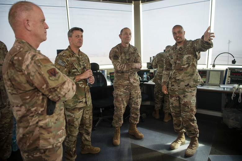 Gen. Mike Holmes, commander of Air Combat Command, Brig. Gen Jason Armagost, 379th Air Expeditionary Wing commander (center left), and Chief Master Sgt. Frank Batten, ACC command chief (left), listen to a control tower mission briefing from Maj. Donald Roley, 379th Expeditionary Operations Support Squadron, during an ACC leadership visit Feb. 11, 2019, at Al Udeid Air Base, Qatar.