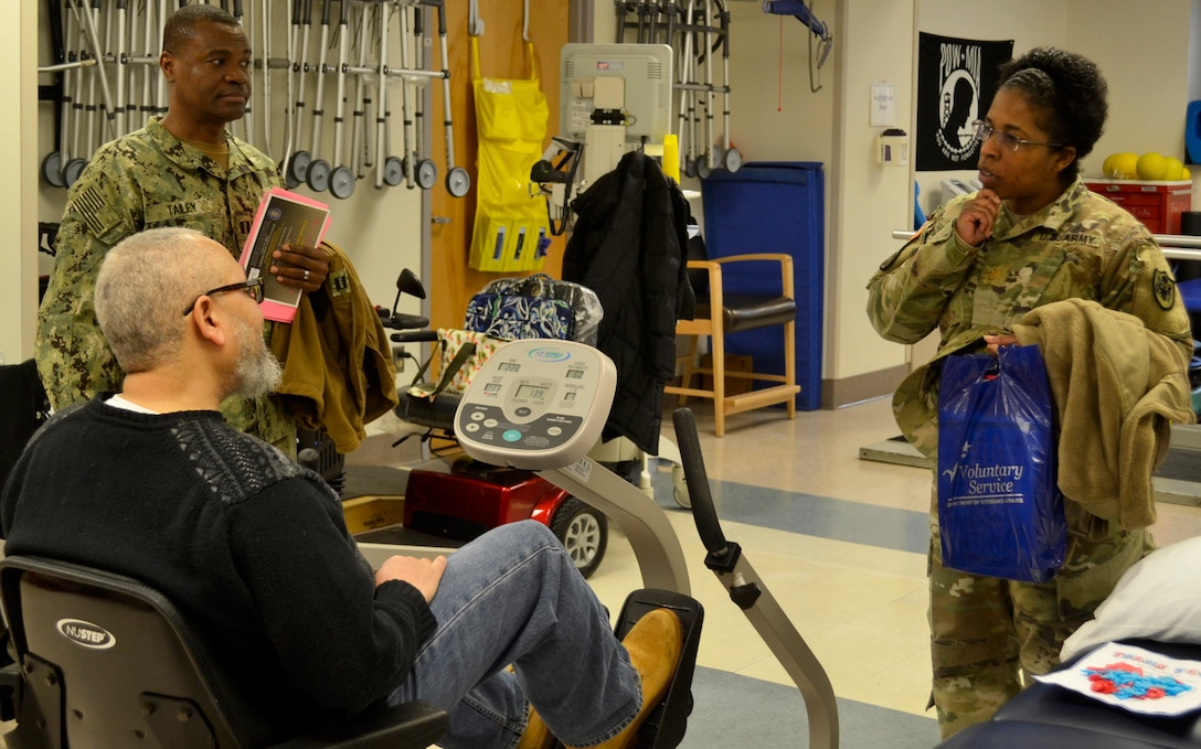 Army Maj. Andrea Jackson, a Medical division chief, right, and Navy Lt. Prince Tailey, a Medical branch chief, top left, listen to a patient receiving therapy care at the Corporal Michael J. Crescenz Veterans Affairs Medical Center, Feb. 11, 2019 in Philadelphia.