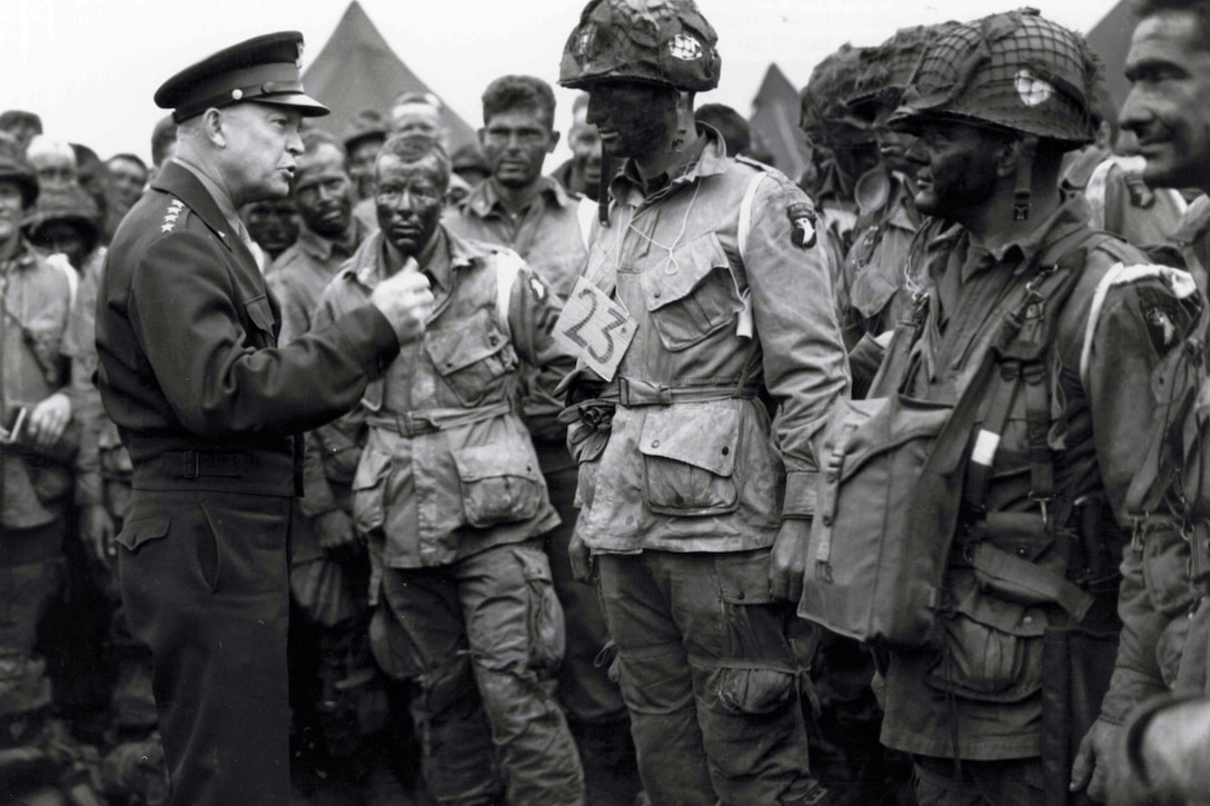 Gen. Eisenhower talks with paratroopers on an airfield in England.
