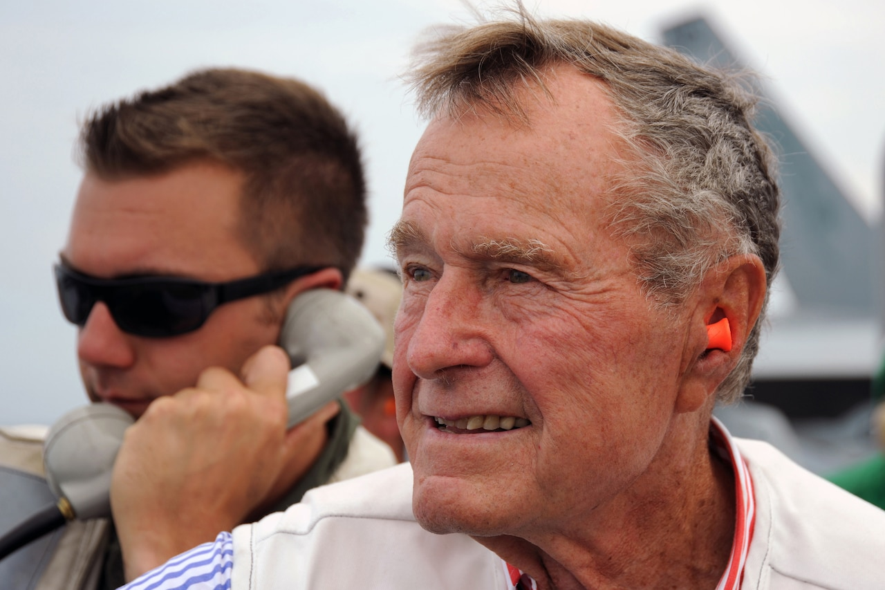 George H.W. Bush wears earplugs as a sailor talks on a phone behind him.