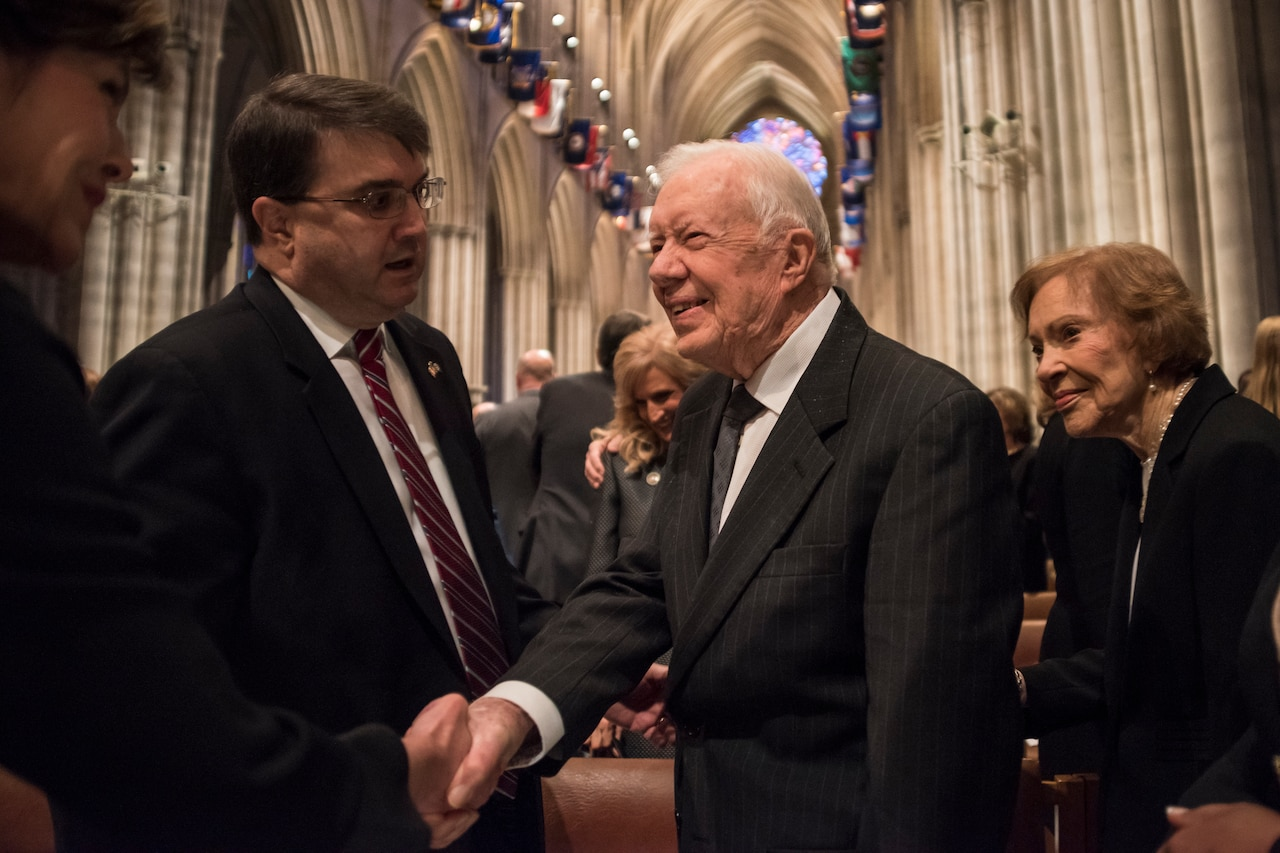 An older man shakes hands with someone else in a cathedral.