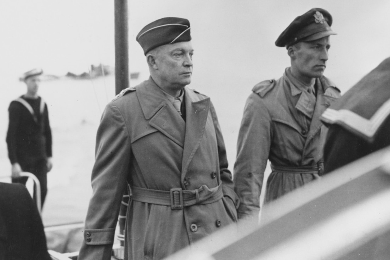 Two high-ranking officers stand on a boat with a sailor in the background.