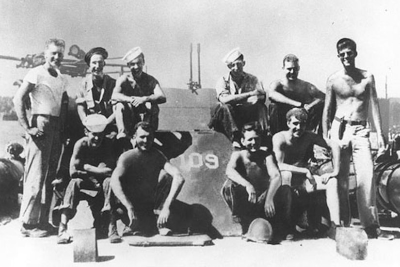 Several sailors pose for a photo on a motor torpedo boat.