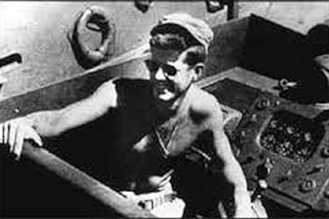A shirtless John F. Kennedy smiles from the driver's seat of a motor torpedo boat.