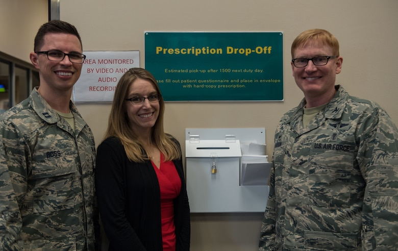 Capt. Angelo Boss, left, 2nd Medical Group Satellite Pharmacy's element chief, Monica Miller, center, key spouse, and Col. Christopher Hudson, right, 2nd MDG commander, pose for a photo in front of a prescription drop box at Barksdale Air Force Base, La., Feb. 4, 2019. There are three drop boxes, one at the entrance, the lobby and the second drive-thru lane at the satellite pharmacy.  (U.S. Air Force photo by Senior Airman Cassandra Johnson)