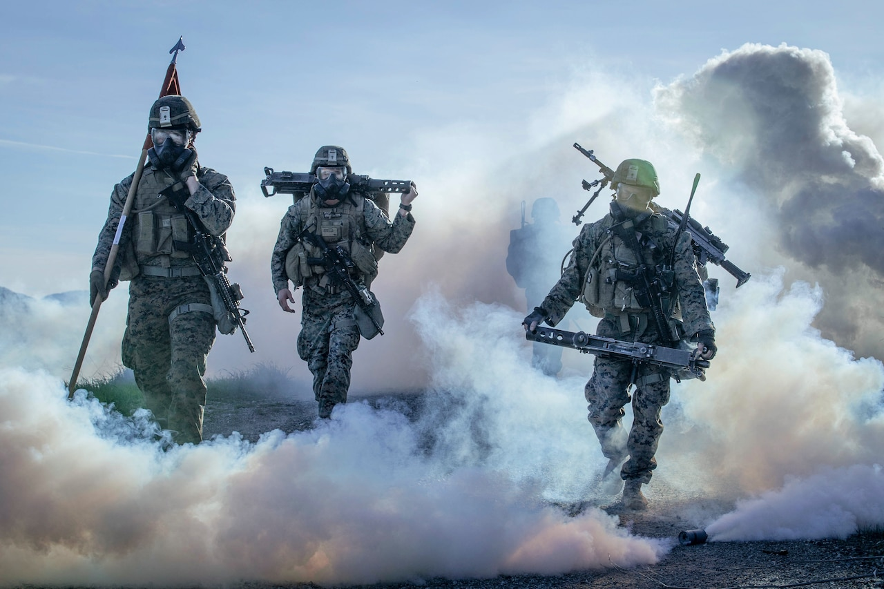 Marines in protective gear hike through smoke.