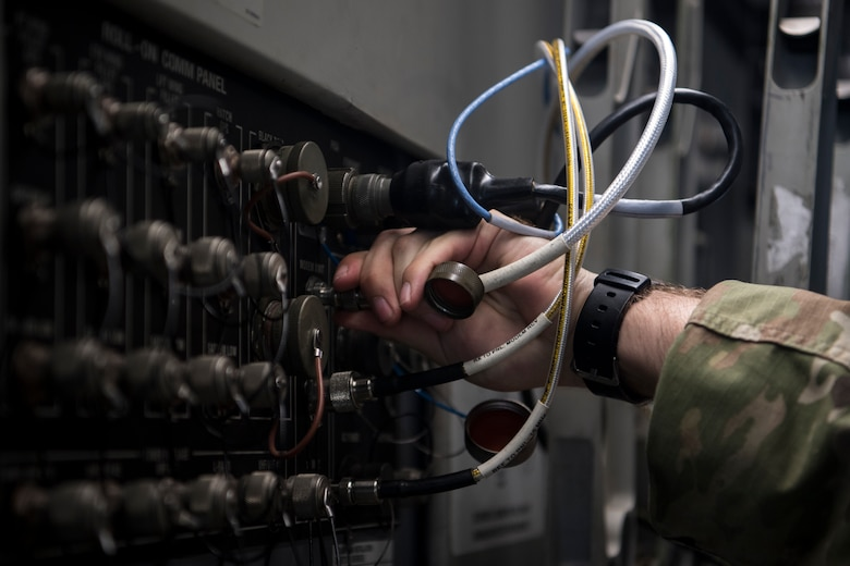 Army Spc. Tristan Sutherland, 50th Expeditionary Signal Battalion satellite communications operator, plugs a communication cable into a C-17 Globemaster III Feb. 7, 2019, at Joint Base Charleston, S.C.