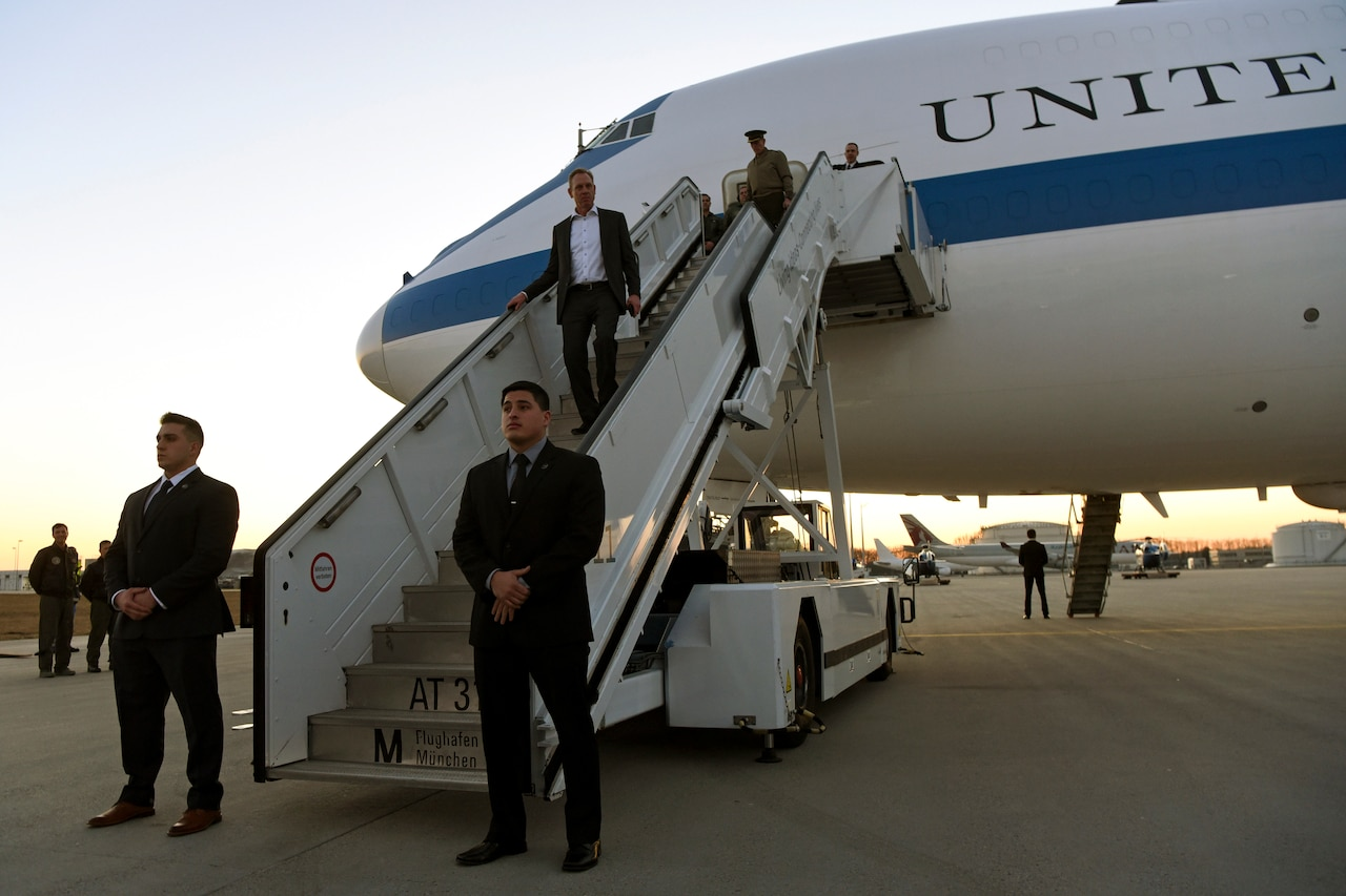 Acting Defense Secretary Patrick M. Shanahan walks down steps of a plane.