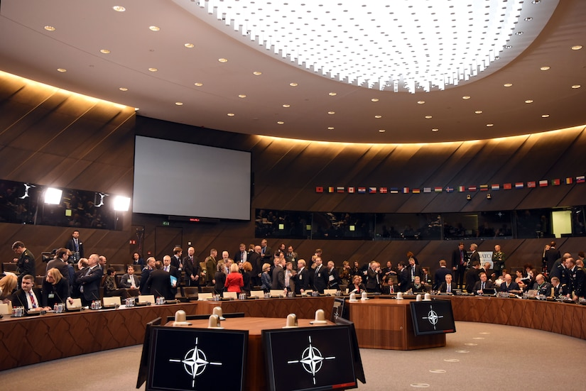 Defense ministers sit at curved tables in a large meeting room.