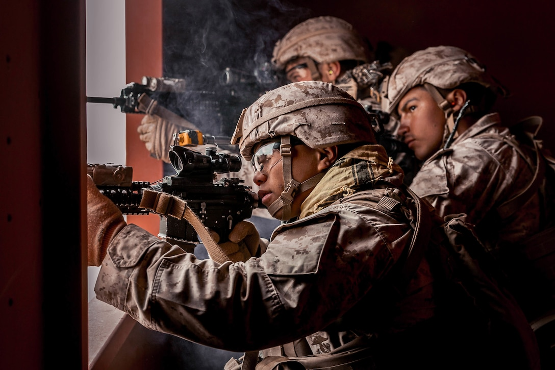 Three Marines, shown in profile, fire weapons out a window.